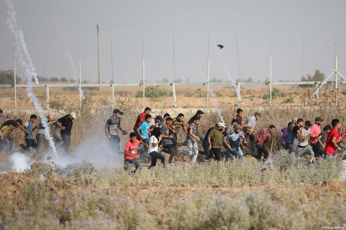 "Israeli forces shower Palestinians with tear gas during a demonstration within the ""Great March of Return"" at Israel-Gaza barrier fence near Al Bureij Refugee Camp in Gaza City, Gaza on July 12, 2019 [Hassan Jedi / Anadolu Agency]"