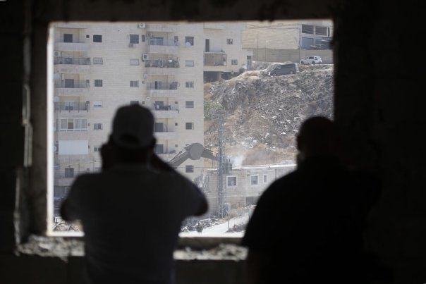 Israeli soldiers demolish a 2 storey building with bulldozers as they have started to demolish buildings belonging to Palestinians on the grounds that the ten buildings are close to wire barriers, which are continuation of the separation wall in Wadi al-Hummus neighborhood of Sur Baher region of East Jerusalem on 22 July 2019. [ Issam Rimawi - Anadolu Agency ]
