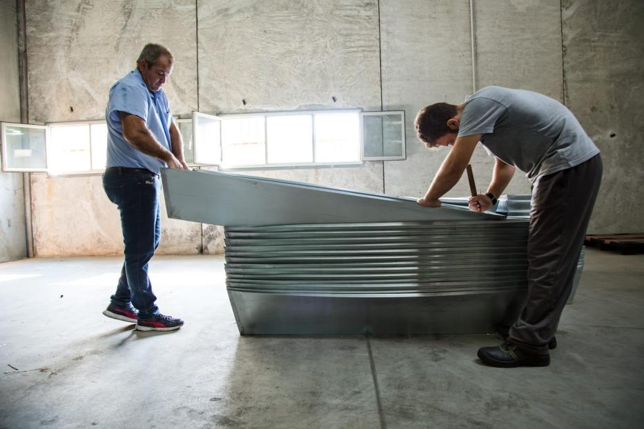 The two mortuary operators assembling the zinc parts of the coffins, in the area of the hangar adjacent to the red zone; the coffins are composed of an internal part in zinc and an external part in wood [Max Hirzel]