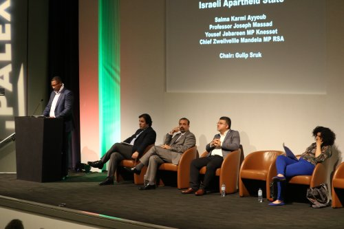 South African MP, Nkosi Zwelivelile Mandela, addresses the crowds at the Palestine Expo 2019 on 6 July 2019 in London, UK. Also on stage, from left to right: Gulip Surk, Professor Joseph Massad, Dr Yousef Jabareen MK, Salma Karmi Ayyoub [Middle East Monitor]