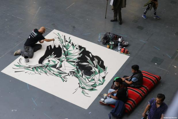 An artist seen painting on a giant canvas at the Palestine Expo 2019 on 6 July 2019 in London, UK [Middle East Monitor]