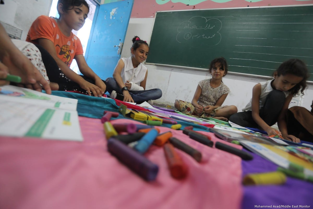 Palestinian children play games at school on 9 July 2019 [Mohammed Asad/Middle East Monitor]