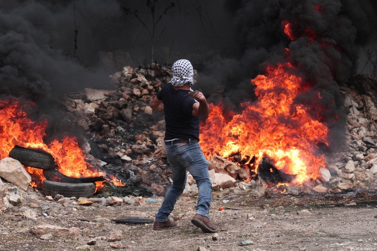 A Palestinian demonstrator throws a stone behind burning tires in response to Israeli forces' intervention in a protest against the construction of Jewish settlements and the separation wall in Qafr Qaddum village in Nablus, West Bank on 2 August 2019. [Nedal Eshtayah - Anadolu Agency]