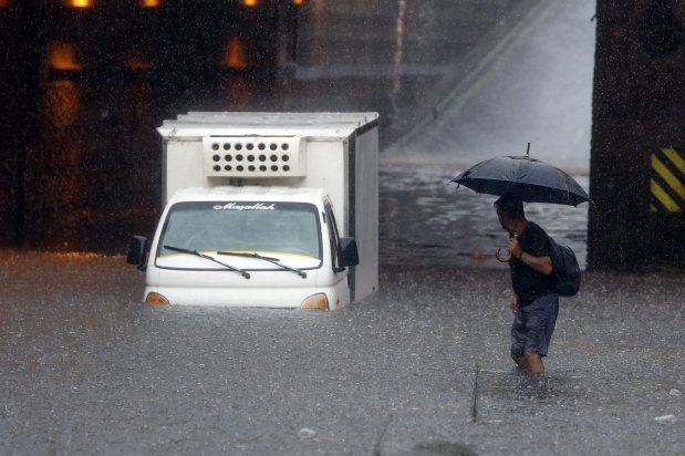 A driver stands on top his flooded car at Aksaray underpass following the heavy rain in Istanbul, Turkey on 17 August 17, 2019 [Serhat Çağdaş/Anadolu Agency]