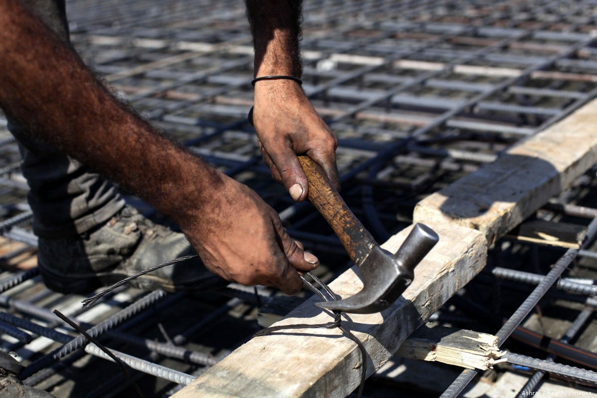 A Palestinian man can be seen working on a construction site [Ashraf Amra/Apaimages]