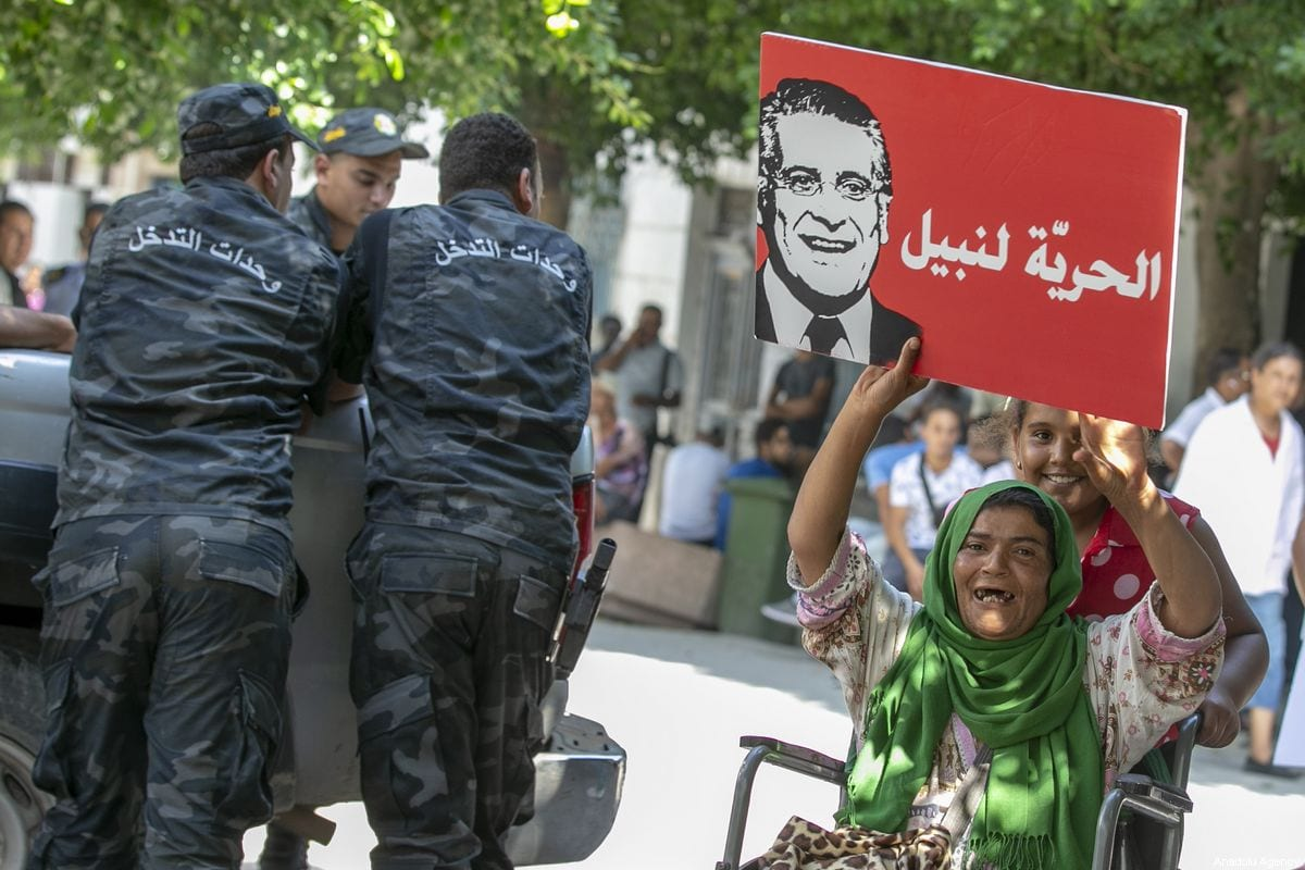 Members of the Tunisian security forces stand guard as supporters of presidential candidate Nabil Karoui carry placards with his image and slogans in his favour as they rally in front of the tribunal in the Tunisian capital Tunis asking for his release from prison on 3 September 2019. [Yassine Gaidi - Anadolu Agency]