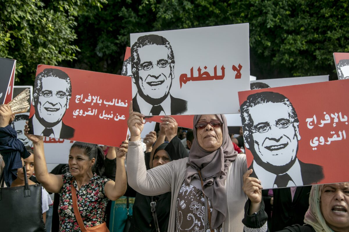 Supporters of presidential candidate Nabil Karoui carry placards with his image and slogans in his favour as they rally in front of the tribunal in the Tunisian capital Tunis asking for his release from prison on 3 September 2019. - [Nacer Talel - Anadolu Agency]