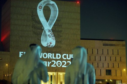 The official logo of the 'FIFA World Cup Qatar 2022' is reflected on a wall of the Qatar National Archive building in Doha, Qatar on 3 September 2019 [Mohammed Dabbous/Anadolu Agency]