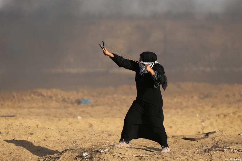 Des Palestiniens lancent des pierres avec des lance-pierres aux forces israéliennes lors d'une manifestation au sein du