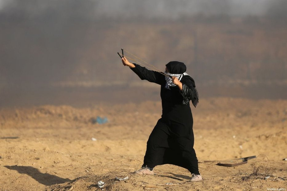 "Palestinians throw stones with using slingshots to Israeli forces during a demonstration within the ""Great March of Return"" at Israel-Gaza border in east of Gaza on 27 September 2019.  [Ashraf Amra - Anadolu Agency]"