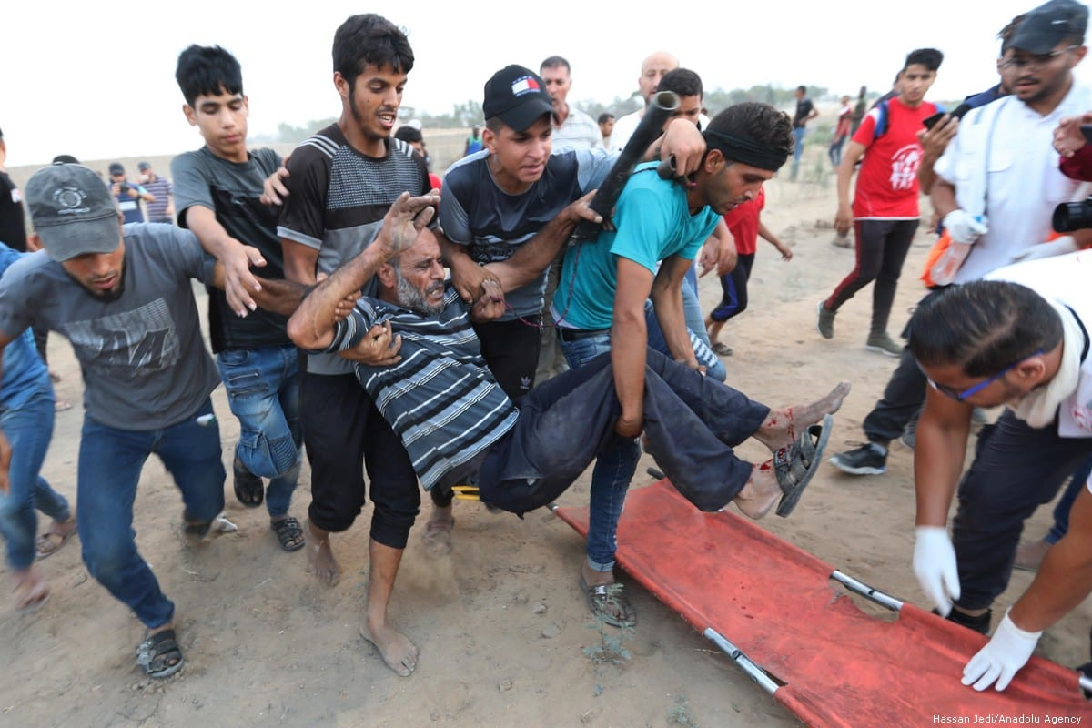 An injured Palestinian is being moved away from the site after Israeli forces attacked protesters during the Great March of Return in Gaza on 13 September 2019 [Hassan Jedi/Anadolu Agency]