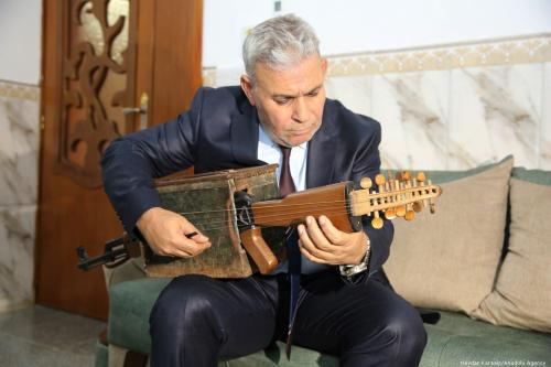 Iraqi music teacher Macid Qazim, poses for a photo with his musical instrument in Baghdad, Iraq on 18 September 2019. Qazim transformed his kalashnikov rifle into a stringed musical instrument [Haydar Karaalp/Anadolu Agency]