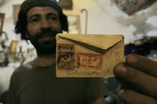Rami Nablusi holding up an old envelope with stamps marking a place and era long gone