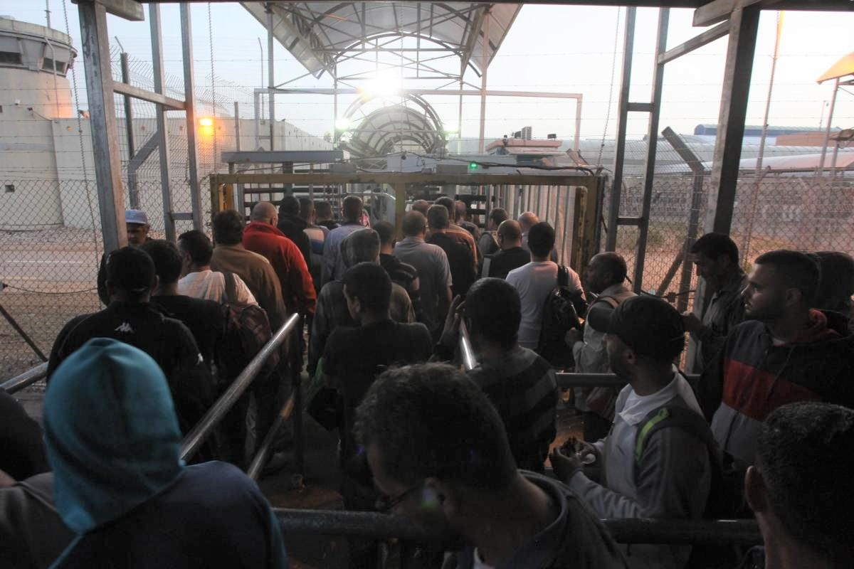 Thousands of Palestinians queue up to cross into Israel and begin their work day as the sun begins to rise, at Eyal Border crossing, in the city of Qalqilya, West Bank on 1 May 2019 [Nedal Eshtayah/Anadolu Agency]