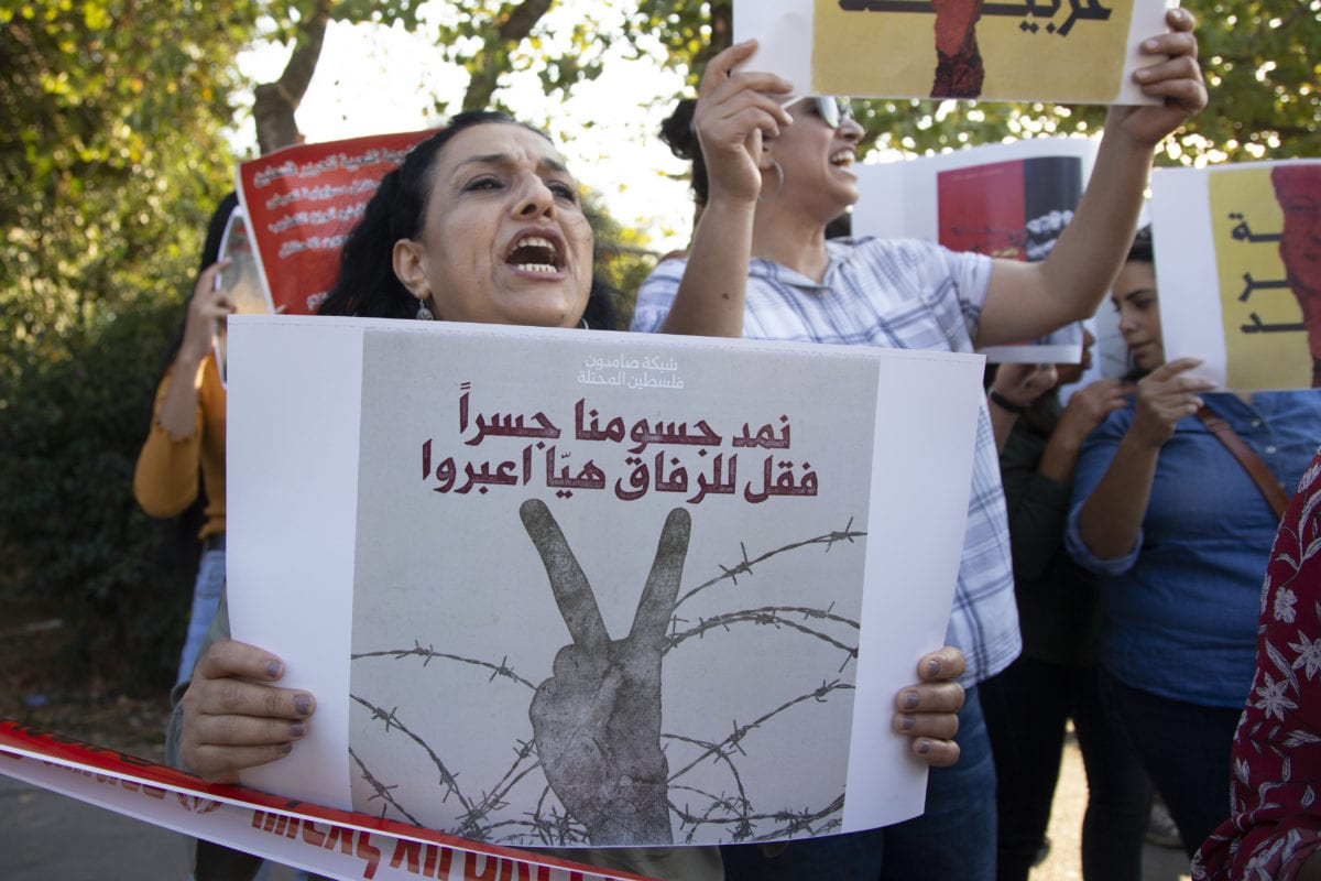 A group of Palestinians shout slogans and hold placards as they gather for a demonstration in support of Palestinian prisoner Samer al-'Arbid, who was arrested by the Israeli army during a raid in the occupied West Bank city of Ramallah last week, in front of the Hadassah Hospital in Jerusalem on 1 October, 2019 [Faiz Abu Rmeleh/Anadolu Agency]