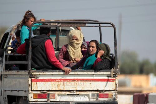 People are being carried in the trunk of a truck as residents continue returning home after Tal Abyad city center was cleared from PKK, listed as a terrorist organization by Turkey, the US and the EU, and Syrian Kurdish YPG militia, which Turkey regards as a terror group, within Turkey's Operation Peace Spring in northern Syria, in Tal Abyad, Syria on 17 October, 2019 [Omer Alven/Anadolu Agency]