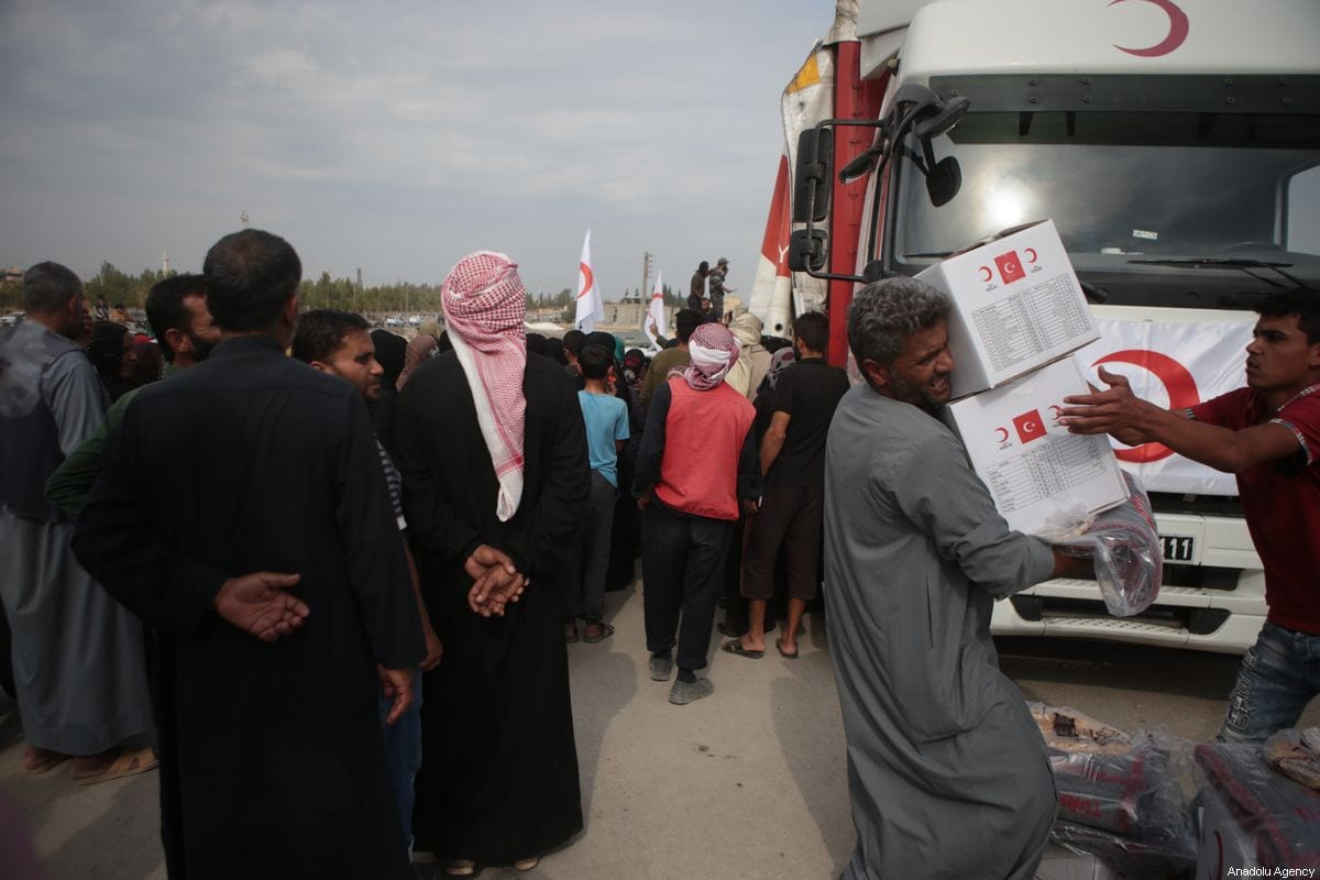 Civilians carry humanitarian aids distributed by Turkish Red Crescent in northern Syria, in Tal Abyad, Syria on October 19, 2019. [Ömer Alven - Anadolu Agency]