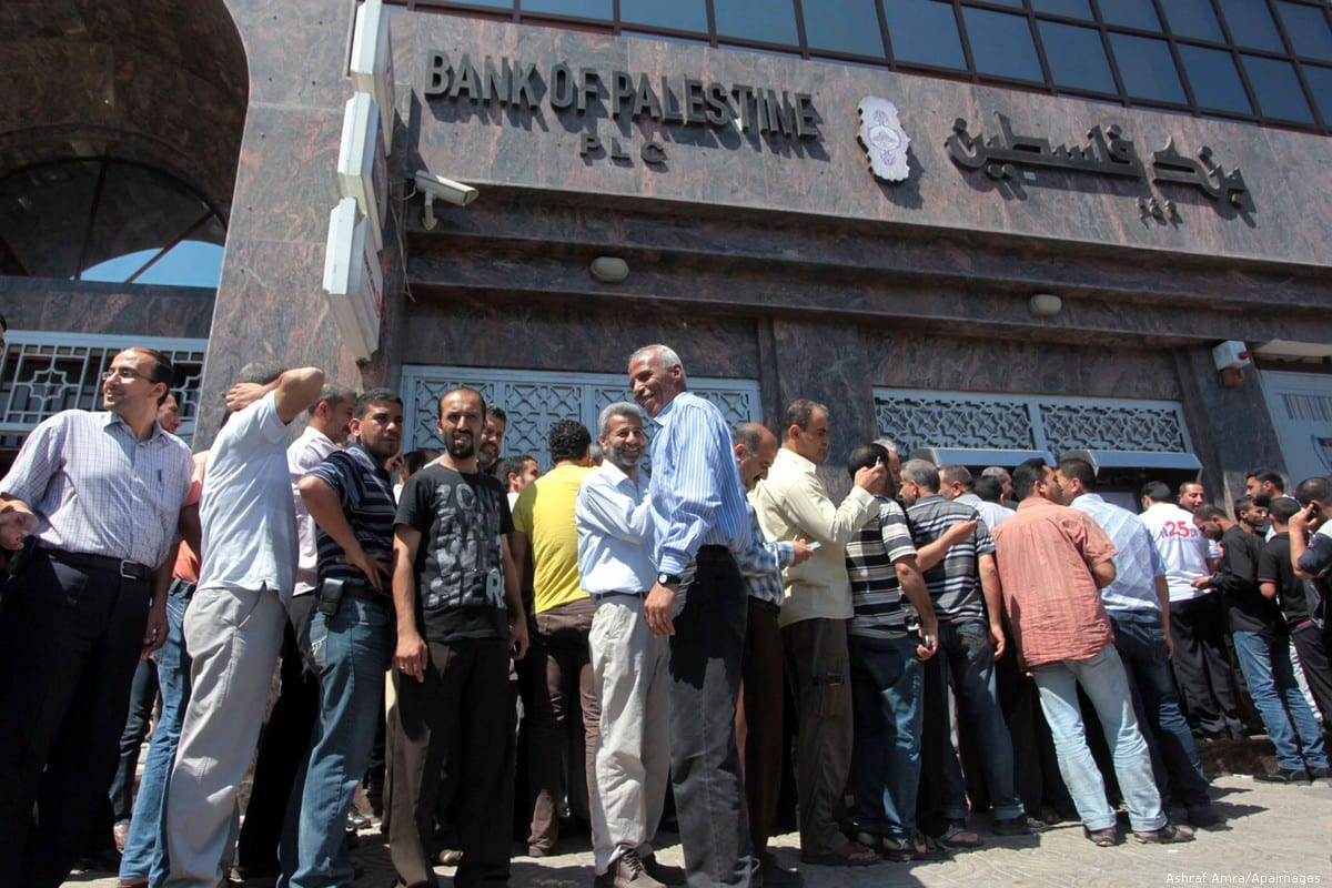 Palestinian employees wait in front of Bank of Palestine to withdrew their salaries from an ATM on 11 June 2014 [Ashraf Amra/Apaimages]
