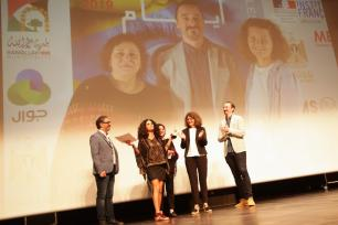 Samaher Al Qadi accepts the Sunbird award for the feature length documentary segment on behalf of Dina Nasr, who was unable to attend the ceremony due to Israel denying her visa [Hamde Abu Rahma]