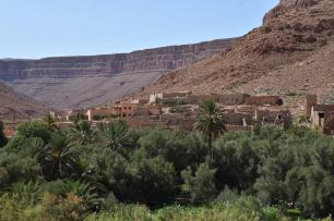 """An old populated settlement stands among a lush oasis in the beginning of the desert region of Morocco, laying between two cliffs in what is known as the """"Gate of the Sahara"""" and the """"Grand Canyon of Morocco."""""""