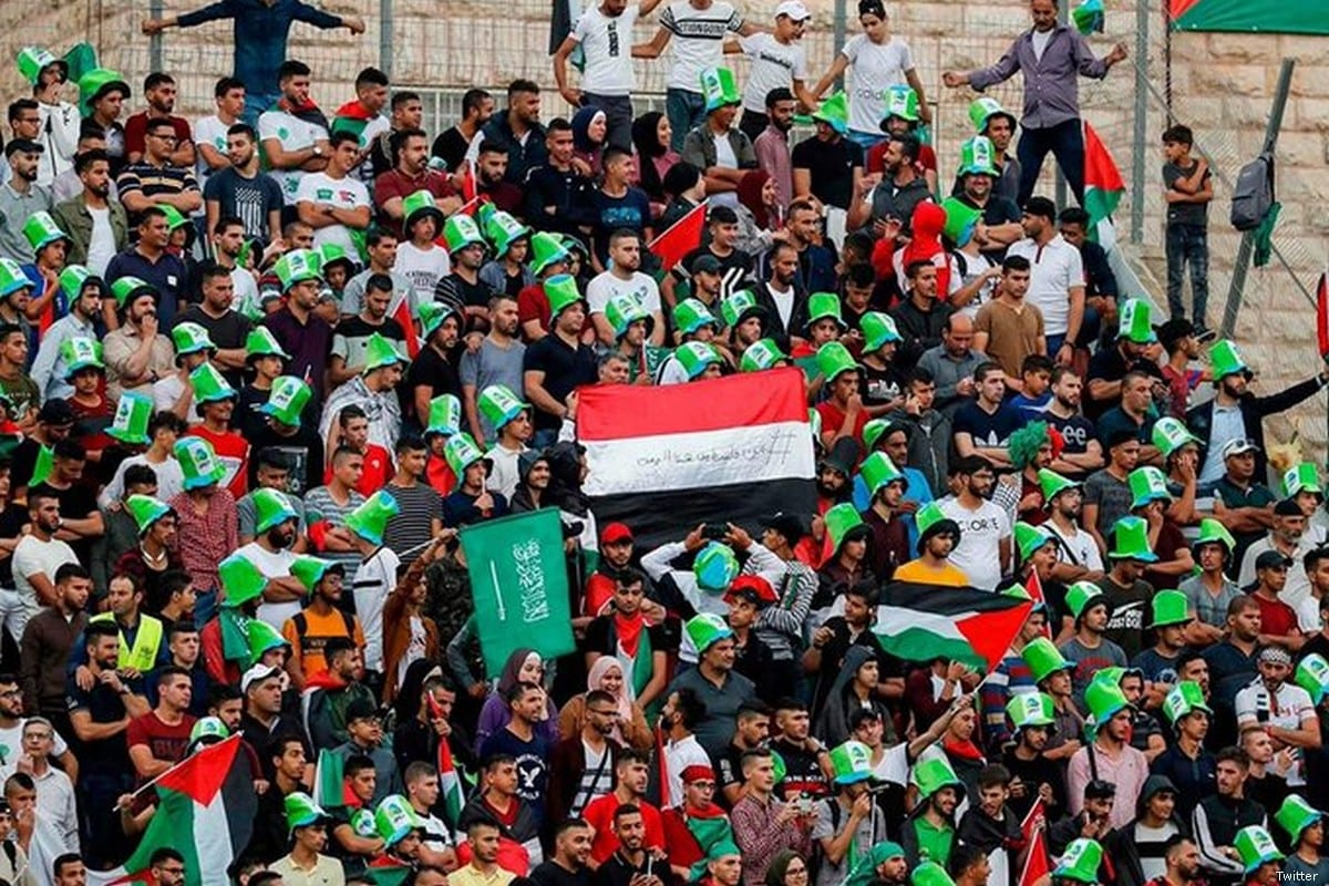 A Palestinian fab raises the Yemeni flag during a football match between Saudi Arabia and Palestine