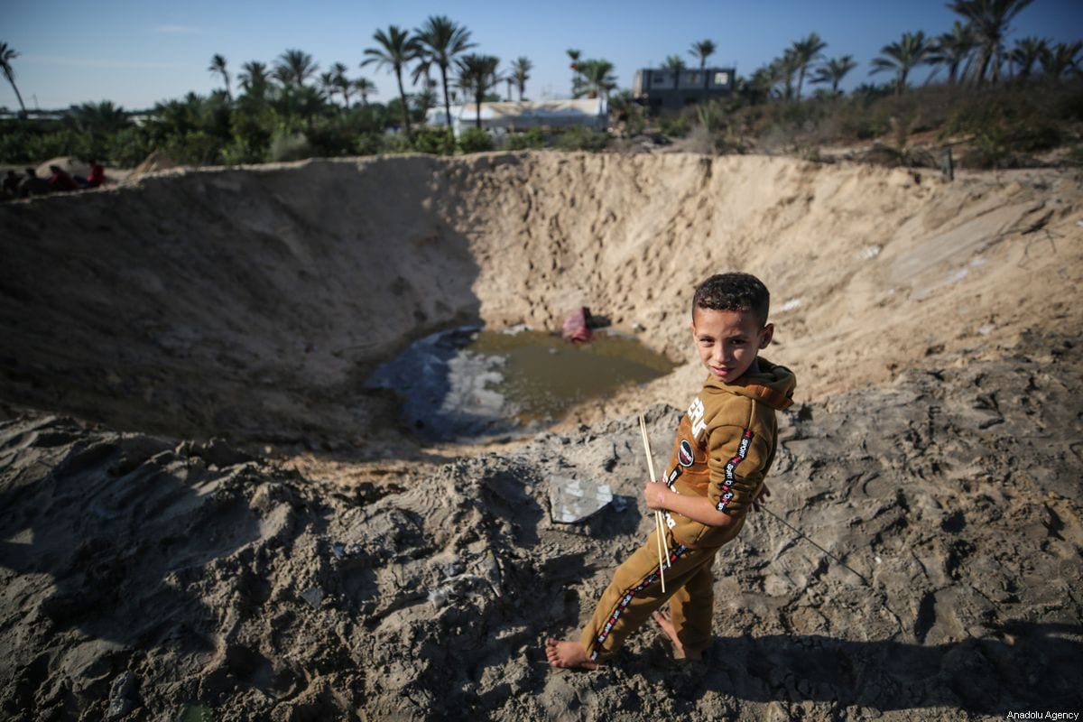 A child stands near a ditch created after Israeli jets bombed an area in northern Gaza late Friday belonging to the Ezzedine al-Qassam Brigades, the armed wing of Palestinian resistance movement Hamas, in Khan Yunis on November 02, 2019 [Mustafa Hassona / Anadolu Agency]