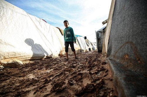 A Syrian boy walks through the mud covered road between tents at the Kefernahum refugee camp, where Syrian refugees live, after heavy rain at the beginning of the winter season in northeastern Idlib, Syria on November 02, 2019. [Izzeddin Idilbi - Anadolu Agency]