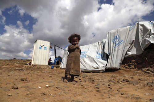 A boy is seen in front of a tent as civilians, who fled from the ongoing civil war where numerous civilian killed, are seen during their daily lives despite many difficulties at Al-Raqah refugee camp in Amran province of northern Sanaa, Yemen on 24 November 2019. [ Mohammed Hamoud - Anadolu Agency ]