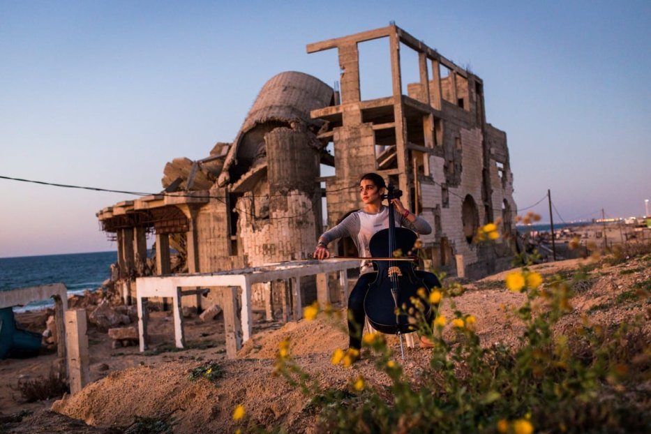 A Palestinain women plays the cello in front of ruins - a still from the film, Gaza