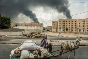 A smoke billows into the sky as two men exchange information on the otherwise empty streets of Shiek Ziyad, in northern Gaza.