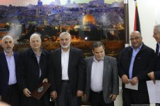 Hamas chief Ismail Haniyeh informs Hanna Nasser, head of the Palestinian Central Election Commission, that Hamas agrees to the plan for holding Palestinian elections [Mohammed Asad/Middle East Monitor]