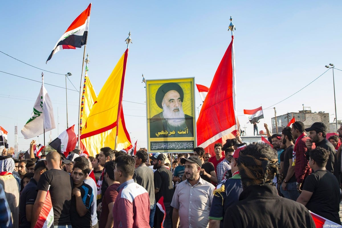 Iraqi demonstrators carry flags and an image of Shiite cleric Ayatollah Ali Husaini al-Sistani, during ongoing anti-government protests in the southern city of Basra on 1 November 2019. [HUSSEIN FALEH/AFP - Getty Images]