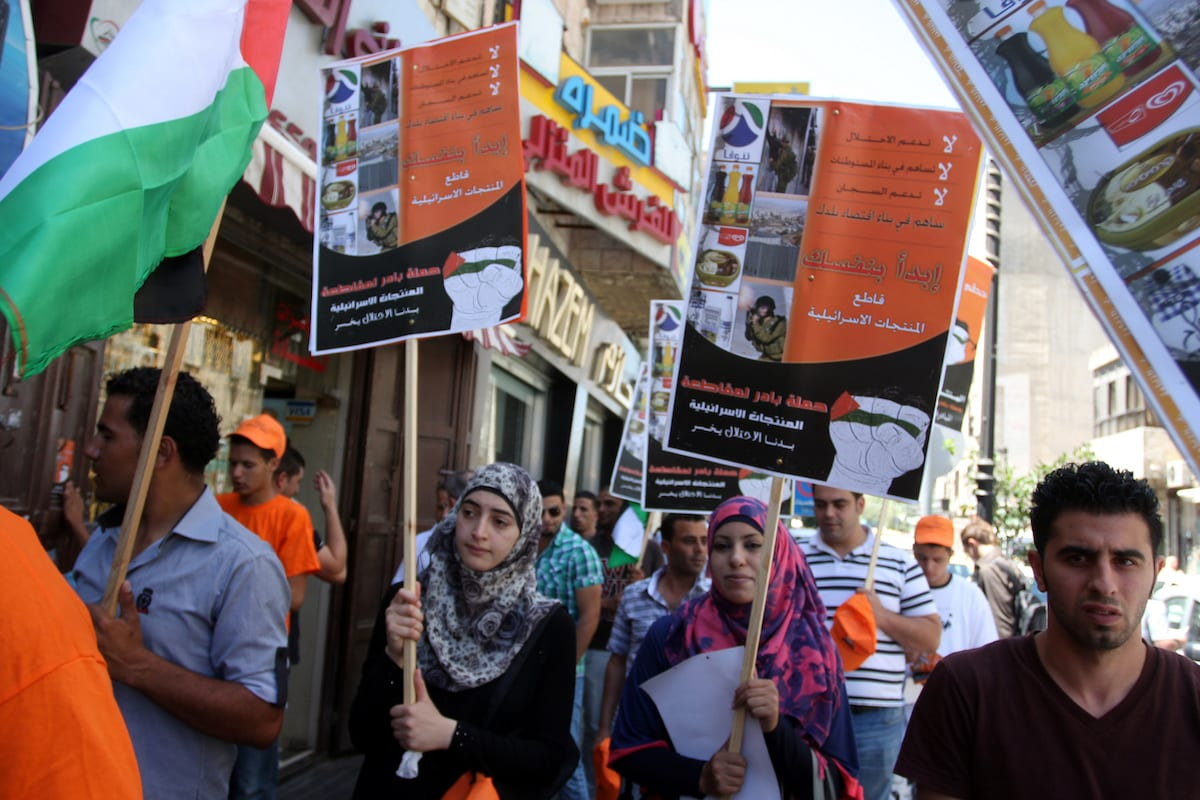 Palestinian protestors hold posters and graphics during a protest demanding Palestinian merchants to boycott Israeli settlement products and goods, and support national economy in the West Bank city of Ramallah ,on 15 July 2012. [Issam Rimawi - Apaimages]