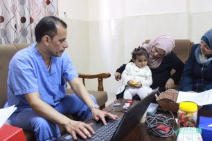 Qatari doctors sit with Palestinian families whose children till undergo ochlear implant operations on 26 November 2019