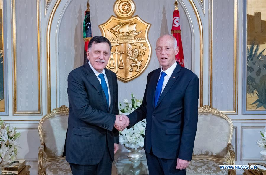 Tunisian President Kais Saied (R) shakes hands with Libya's UN-backed Prime Minister Fayez al-Sarraj during their meeting in Tunis, Tunisia, on 10 December, 2019 [Tunisian presidency handout]