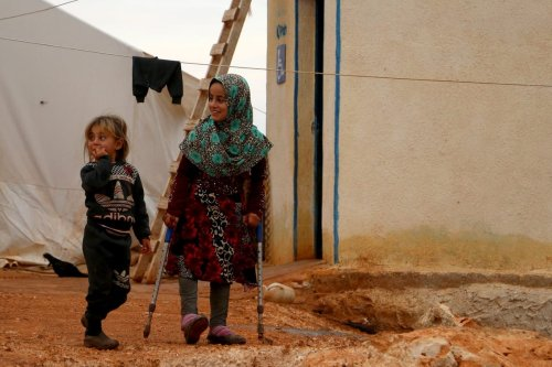 9-year-old Syrian Maya Meri (R) is seen after receiving prosthetic legs at a rehabilitation clinic last year in Turkey, on 8 December, 2019 in Idlib, Syria [Muhammed Abdullah/Anadolu Agency]