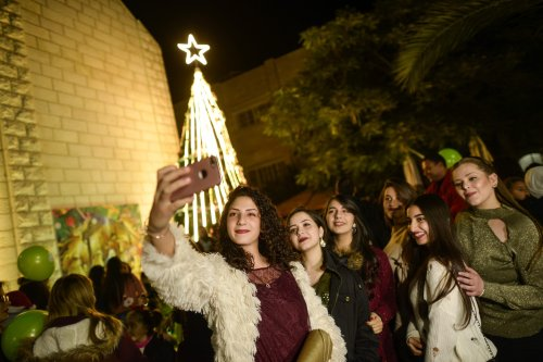 People gather around Christmas tree at Latin Church in Gaza City, Gaza on 14 December 2019 [Mustafa Hassona/Anadolu Agency]