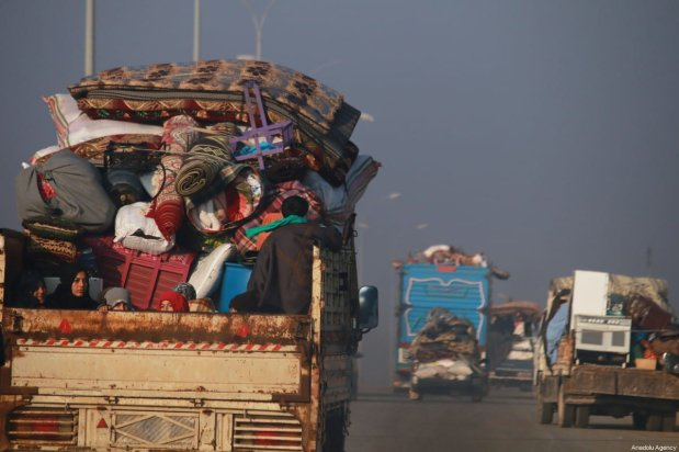 Syrian families fleeing the ongoing attacks by the Assad regime and Russia, are seen on their way towards Turkey, with their belongings, on December 20, 2019 in Idlib, Syria [Ekrem Masri / Anadolu Agency]