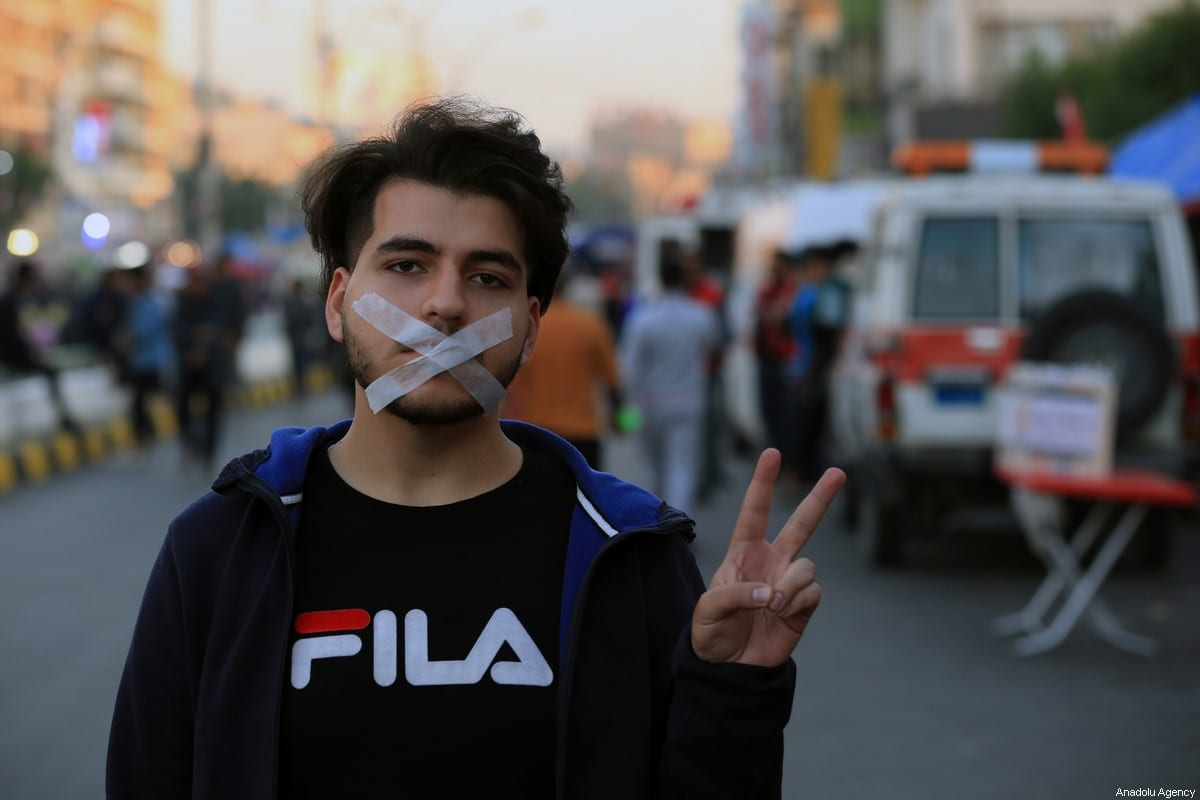 A protester bands his mouth during a hunger strike for their demands as they continue their anti-government demonstrations at Tahrir Square in Baghdad, Iraq on December 23, 2019 [Murtadha Sudani / Anadolu Agency]