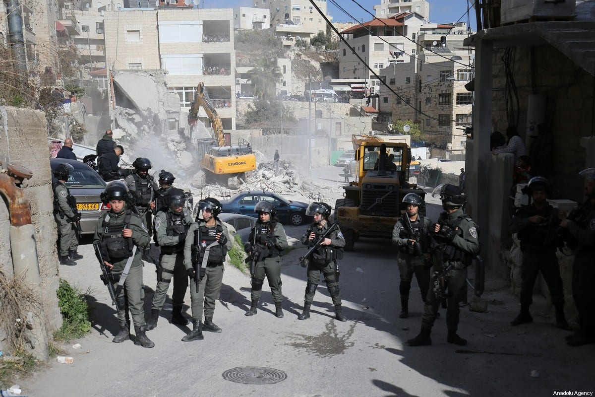 Israeli forces stand guard as a Palestinian building is demolished by Israeli forces in Isawiya district of Eastern Jerusalem on December 24, 2019 [Mostafa Alkharouf / Anadolu Agency]