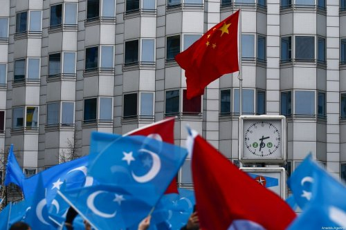 Demonstrators hold Uyghur flags as they take part in a demonstration in support of Uyghur Turks against human rights violations of China, in Berlin, Germany on 27 December 2019 [Abdulhamid Hoşbaş/Anadolu Agency]