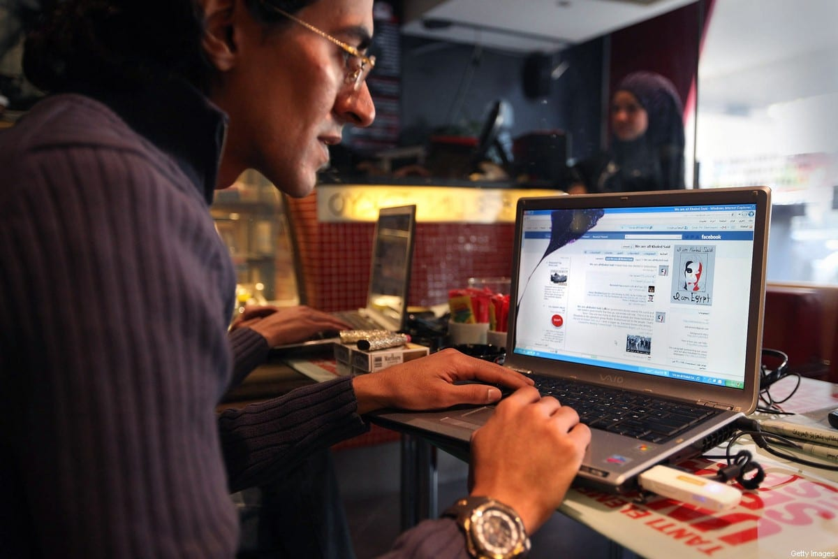 A man looks at a laptop displaying a Facebook page in a cafe on January 27, 2011 in Cairo, Egypt [Peter Macdiarmid/Getty Images]