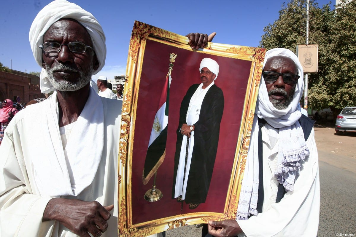 Supporters of deposed Sudanese president Omar al-Bashir lift a picture of him during a rally near the presidential palace in the capital Khartoum after his conviction of graft, on December 14, 2019 [EBRAHIM HAMID/AFP via Getty Images]