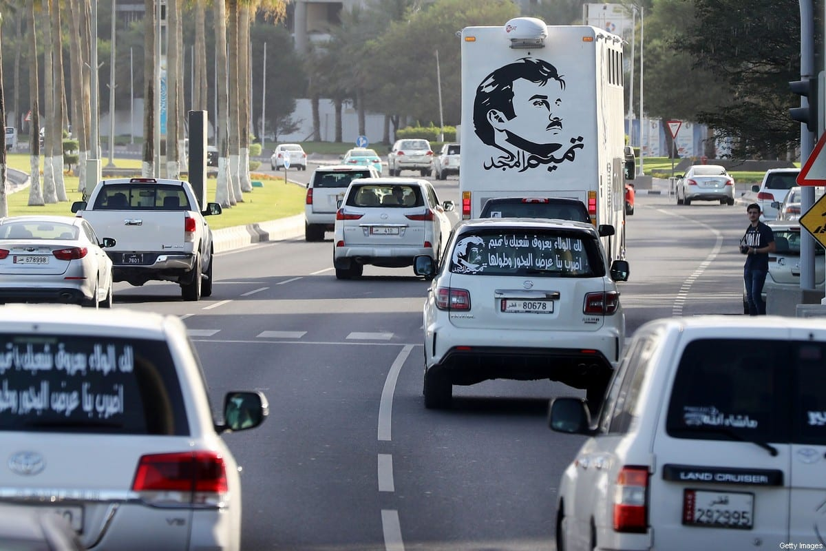 "A general view taken on June 11, 2017 shows portraits of Qatar's Emir Sheikh Tamim bin Hamad Al-Thani on the back of vehicles and text reading in Arabic: ""Tamim the glorious"" in Doha after the diplomatic crisis surrounding Qatar and the other Gulf countries spilled from social media to more traditional forms of media -- all the way back to billboards [KARIM JAAFAR/AFP via Getty Images]"