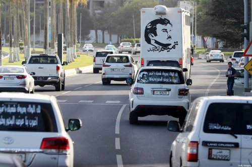 """A general view taken on June 11, 2017 shows portraits of Qatar's Emir Sheikh Tamim bin Hamad Al-Thani on the back of vehicles and text reading in Arabic: """"Tamim the glorious"""" in Doha after the diplomatic crisis surrounding Qatar and the other Gulf countries spilled from social media to more traditional forms of media -- all the way back to billboards [KARIM JAAFAR/AFP via Getty Images]"""