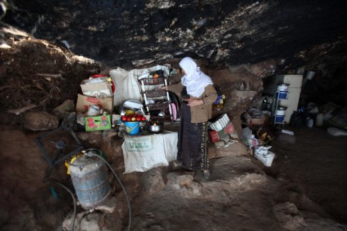 A Palestinian woman prepares a meal for her children at her cave near the West Bank city of Hebron, 24 July 2013 [Mamoun Wazwaz/Apaimages]