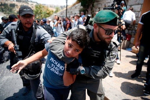 Israeli forces detain a Palestinian youth in Jerusalem on 17 July 2017 [AHMAD GHARABLI/AFP/Getty Images]