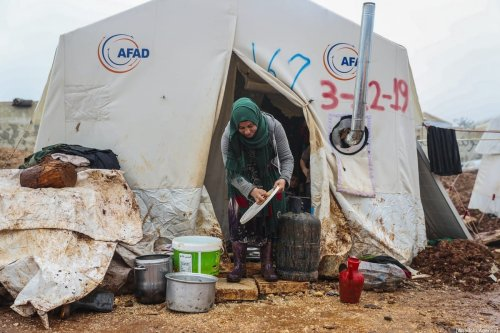 Syrian woman is seen in front of her tent at a camp hosting Syrian families, who have been forced to displace due to the attacks carried out by Assad regime and Russia, in Idlib, Syria on January 10, 2020 [Esra Hacioğlu/Anadolu Agency]