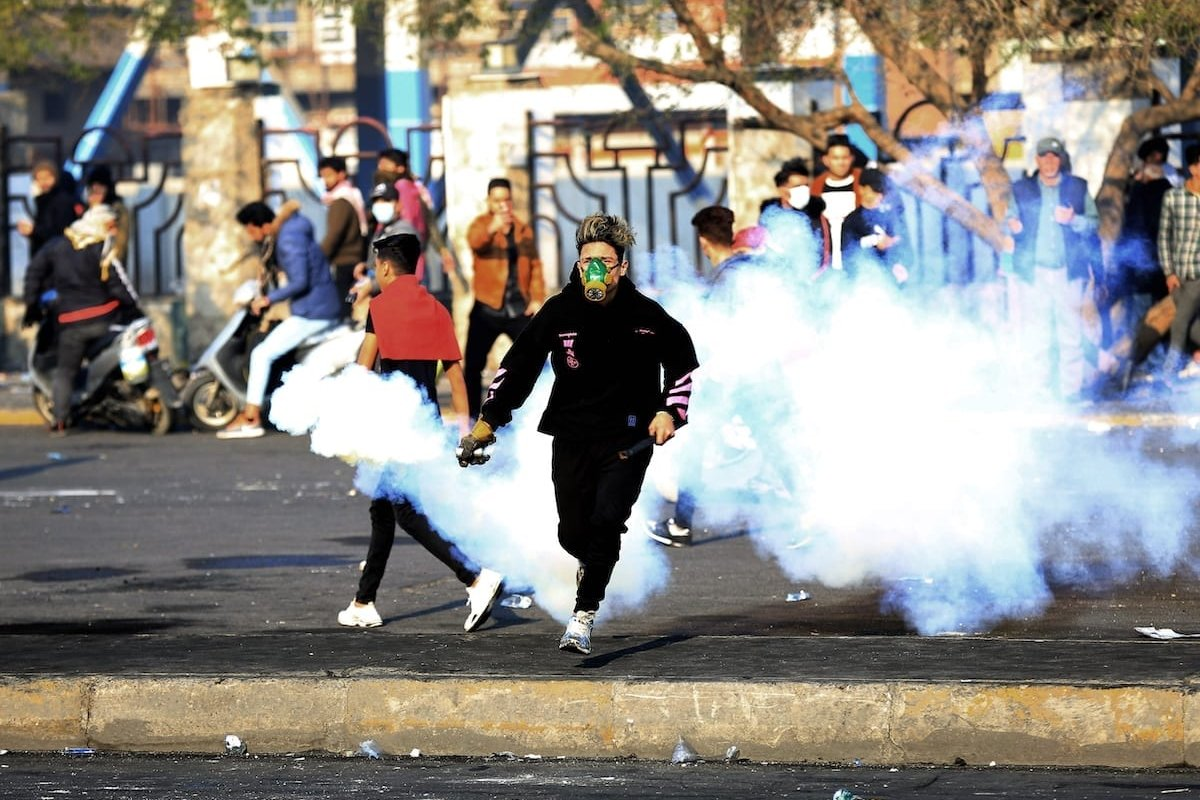 Security forces intervene protesters with tear gas canisters during the anti-government protest around Tahrir Square in Baghdad, Iraq on 20 January, 2020 [Murtadha Sudani/Anadolu Agency]