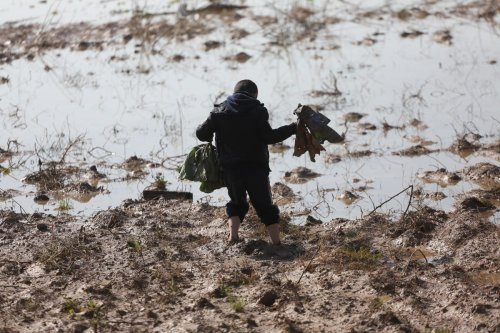 A Palestinian boy stuck in mud after Israel forces opened rainwater stores allowing water to flood Gaza on 15 January 2020 [Mohammed Asad/Middle East Monitor]